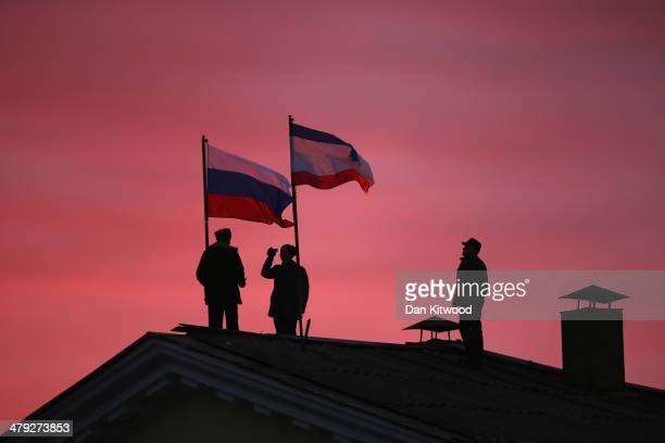 Cossack men install a Russian flag and a Crimean flag on the roof of the City Hall building on March 17 2014 in Bakhchysarai Ukraine People in Crimea...