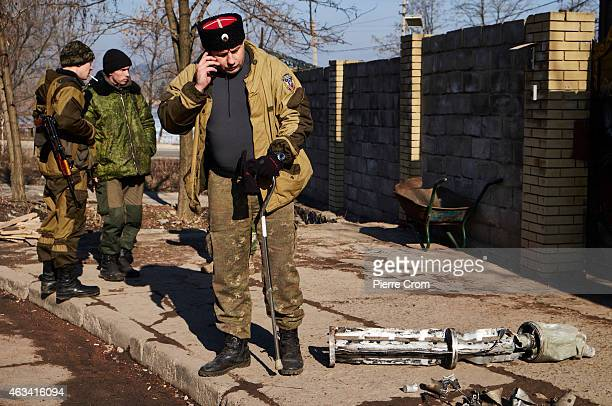 Cossack officer makes a phone call near the remains of a missile outside the Cossack base as fighting continues in the area on February 14 2015 in...