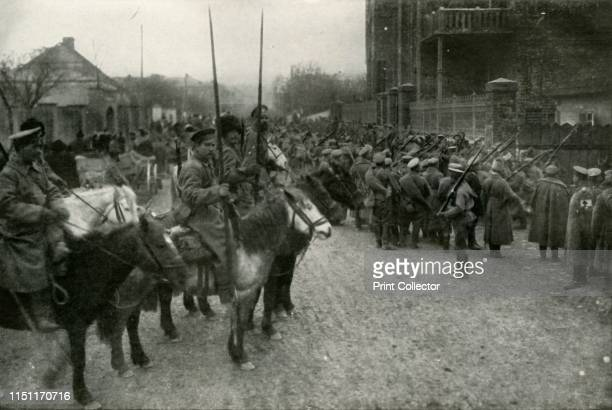 Cossack Patrol and Russian Infantry', . Scene from the First World War, 1914-1919: 'In a town only just evacuated by the retreating Germans, the...