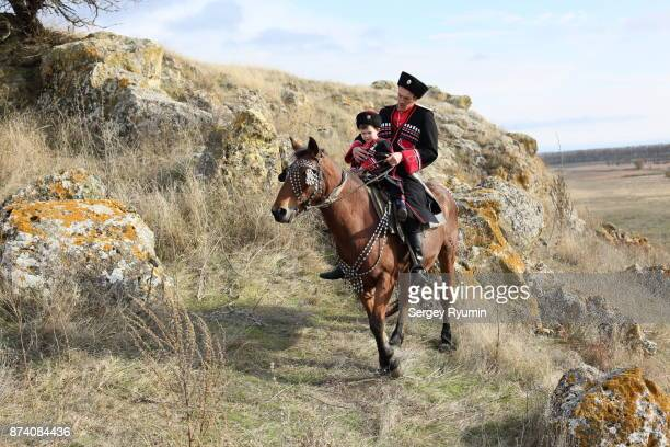 Cossack with his son riding a horse.