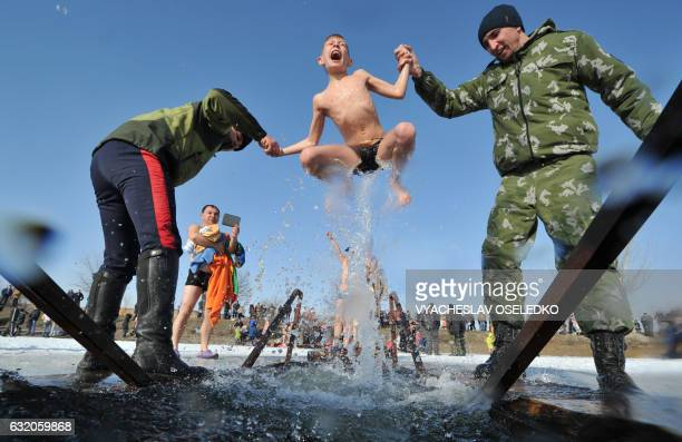 TOPSHOT Cossacks help a boy to take a bath in the icy waters of a lake during the celebration of the Epiphany holiday near the village of Leninskoe...
