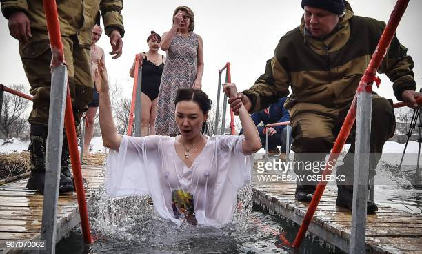 Cossacks help a woman to take a bath in the icy waters of a river during the celebration of the Epiphany holiday near the village of Baytik some 15...