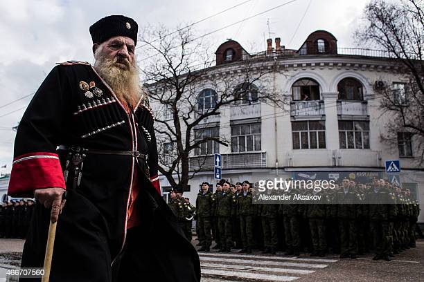 Cossacks march through the streets as people celebrate the first anniversary of the signing of the decree on the annexation of the Crimea by the...