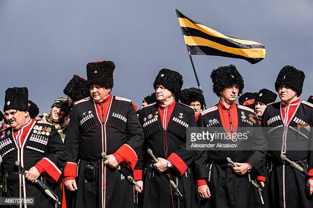 Cossacks stand near the Monument To A Mariner and A Soldier as people celebrate the first anniversary of the signing of the decree on the annexation...