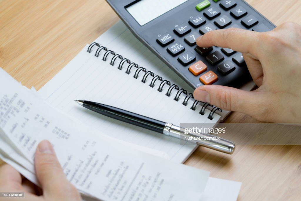 Cost calculation or bill payment concept, hand put finger on calculator and black pen on paper notepad with pile of bills in the left hand on wooden table : Stock Photo