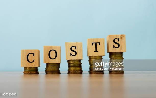 Cost text written on wooden block with stacked coins