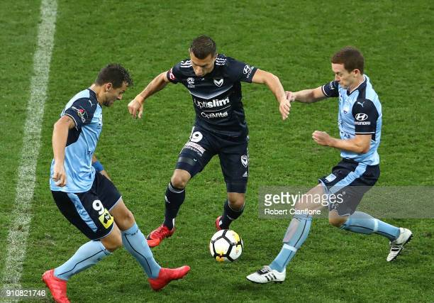 Costa Barbarouses of the Victory is challenged by Bobo and Brandon O'Neill of Sydney FC during the round 18 ALeague match between Melbourne Victory...