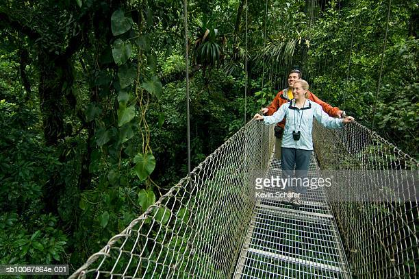 Costa Rica, Arenal Volcano area, couple on rainforest canopy walkway