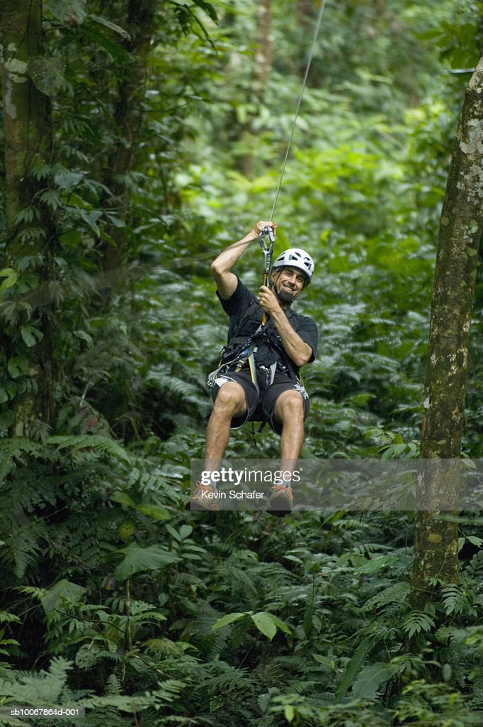 Costa Rica Aventuras del Sarapiqui man on canopy tour zipline in forest  Stock & Costa Rica Aventuras Del Sarapiqui Man On Canopy Tour Zipline In ...