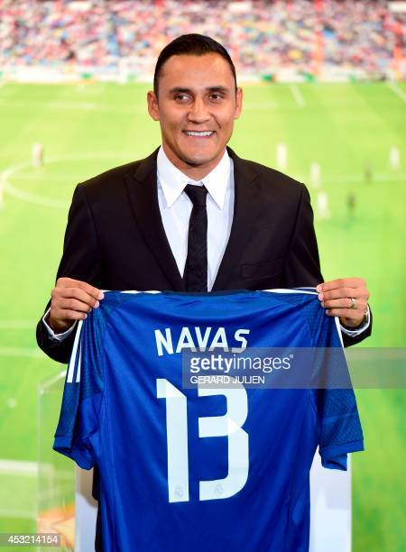 Costa Rica goalkeeper Keylor Navas poses with his new team's jersey during his presentation at the Santiago Bernabeu stadium following his signing...