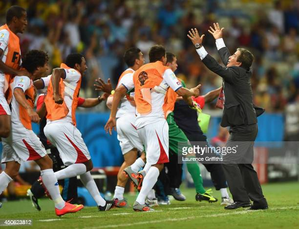 Costa Rica players celebrate with head coach Jorge Luis Pinto after their teams third goal during the 2014 FIFA World Cup Brazil Group D match...