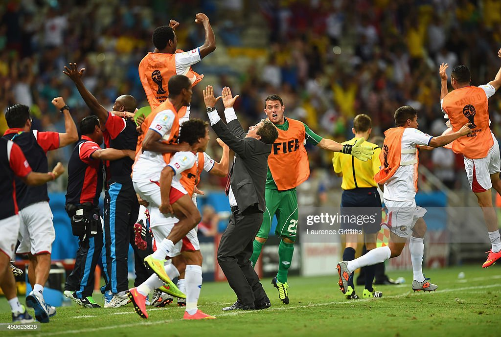 Costa Rica players celebrate with head coach Jorge Luis Pinto after their teams third goal during the 2014 FIFA World Cup Brazil Group D match between Uruguay and Costa Rica at Castelao on June 14, 2014 in Fortaleza, Brazil.