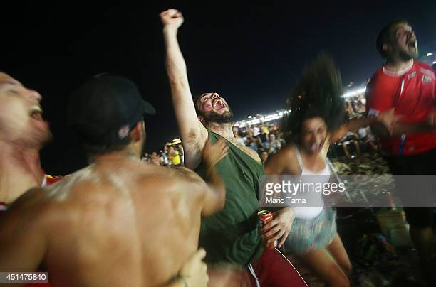 Costa Rica supporters celebrate before their shootout win over Greece while watching the FIFA Fan Fest live broadcast on Copacabana Beach on June...