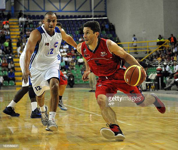 Costa Rican Cristian Chavarria and Mario Amador of Honduras play during their basketball match during the 10th Central American Games in San Jose on...