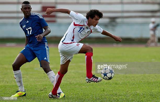 Costa Rican footballer Yeltsion Tejeda takes control of the ball over Cuban Heviel Cordovez during a friendly match on December 11 2011 in Havana The...