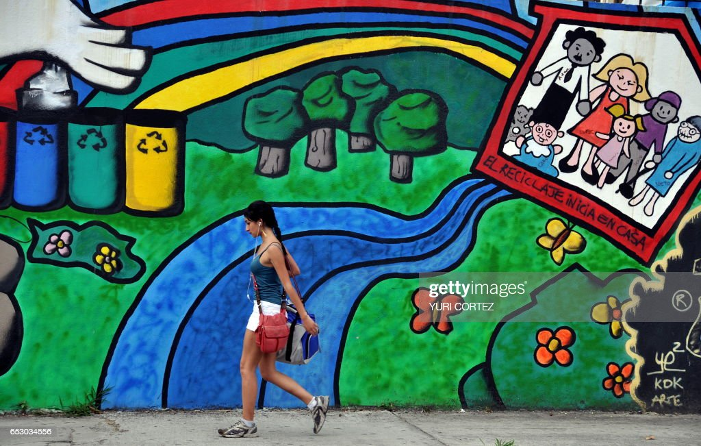 A Costa Rican girl walks past a mural in favor of recycling and the environment on a street of San Jose, on March 10, 2010. Costa Rica is a country known for its environmental protection policies, and where 25 percent of the land and part of the waters have been declared National Parks and Protection Areas since the 70s. In addition, several private initiatives are dedicated to protecting the environment, often with the help of international organizations or universities. The mural reads 'Recycling starts at home'. AFP PHOTO/ Yuri CORTEZ /