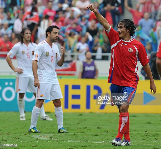 Costa Rican Randall Brenes celebrates after scoring against Spain while Spaniards David Villa and Carles Pujol show their dejection during a friendly...