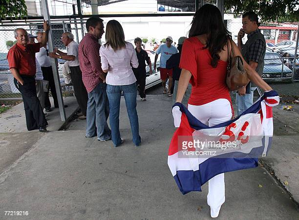 A Costa Rican woman holds a national flag with a Yes written on it as she leaves the polling station during the referendum to approve a free trade...