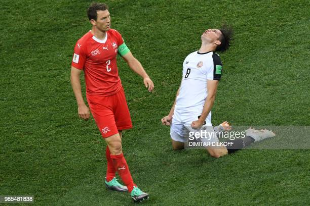 TOPSHOT Costa Rica's defender Bryan Oviedo reacts next to Switzerland's defender Stephan Lichtsteiner during the Russia 2018 World Cup Group E...