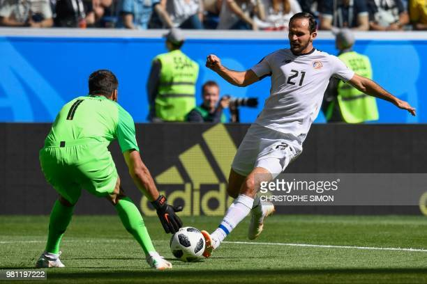 Costa Rica's forward Marco Urena attempts a shot shot on Brazil's goalkeeper Alisson during the Russia 2018 World Cup Group E football match between...