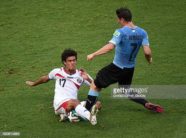 Costa Rica's midfielder Yeltsin Tejeda and Uruguay's midfielder Cristian Rodriguez vie for the ball during a Group D football match between Uruguay...