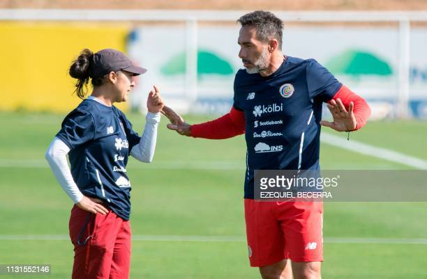 Costa Rica's national women's football team coach Amelia Valverde talks with Costa Rican national football team coach Gustavo Matosas before a...