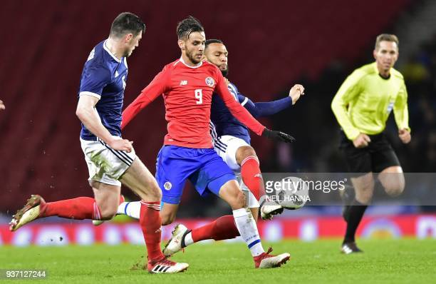 Costa Rica's striker Yendrick Ruiz vies with Scotland's midfielder Scott McKenna and Scotland's midfielder Matthew Phillips during the International...