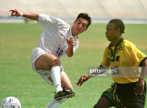 Costar Rican soccer player Jose Calderon fights for the ball with Jamaican defender Marco MacDonald 12 August in the Pachencho Romero Stadium in...
