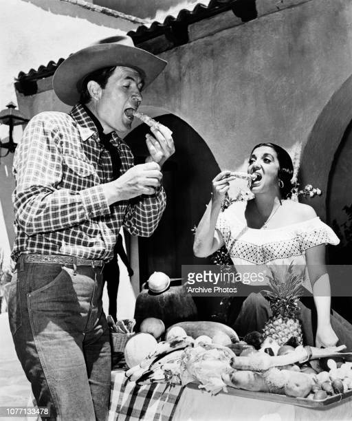 Costars Fess Parker and Katy Jurado eating on the set of the western film 'Smoky' circa 1966