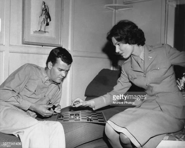 Costars Jim Hutton and Paula Prentiss playing checkers on the set of the MGM film 'The Horizontal Lieutenant' 1961 They are wearing US military...