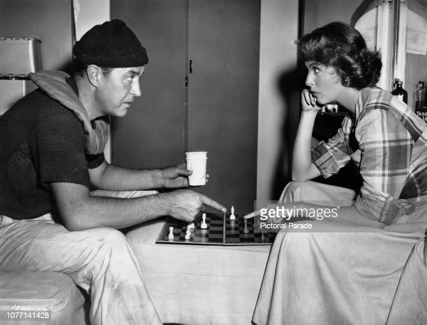 Costars Ray Milland and Arlene Dahl play chess in costume on the set of the film 'Jamaica Run' 1952