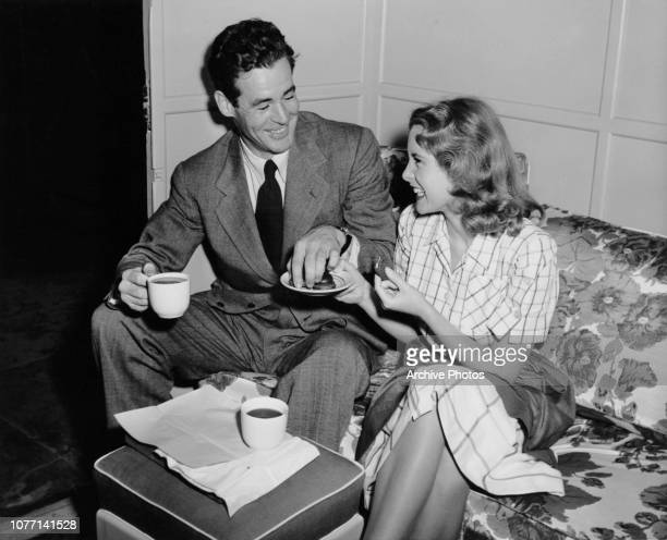 Costars Robert Ryan and Janet Leigh share coffee and biscuits on the set of the MGM film 'Act Of Violence' 1948