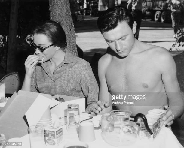 Costars Shirley MacLaine and Laurence Harvey eat a packed lunch on the set of the MGM film 'Two Loves' aka 'The Spinster' circa 1960