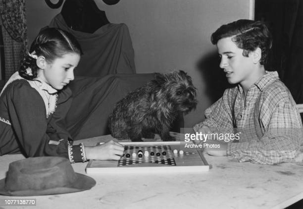 Costars Virginia Weidler and Gene Reynolds playing Chinese checkers on the set of the MGM film 'Patsy' later titled 'Bad Little Angel' 1939 They are...
