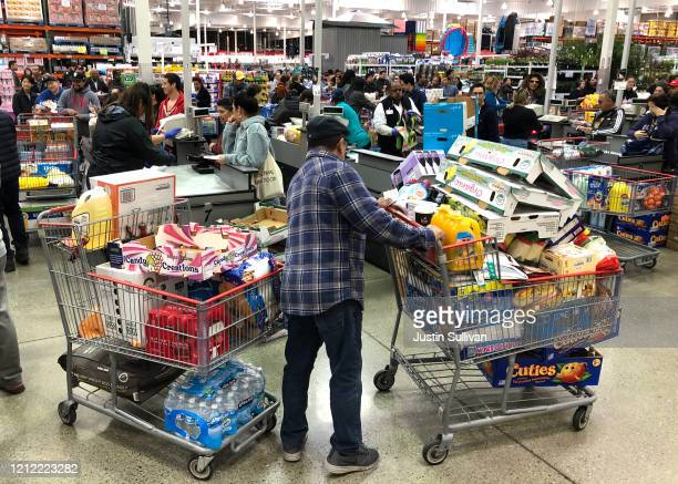 Costco customer stands by his two shopping carts at a Costco store on March 13 2020 in Richmond California Some Americans are stocking up on food...