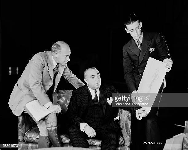 Costume designer Adrian showing one of his sketches to filmmaker Cecil B DeMille and a producer for MGM Studios January 18th 1929