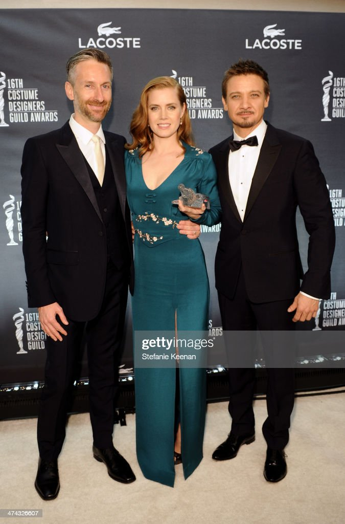Costume designer Michael Wilkinson, actress Amy Adams and actor Jeremy Renner attend the 16th Costume Designers Guild Awards with presenting sponsor Lacoste at The Beverly Hilton Hotel on February 22, 2014 in Beverly Hills, California.