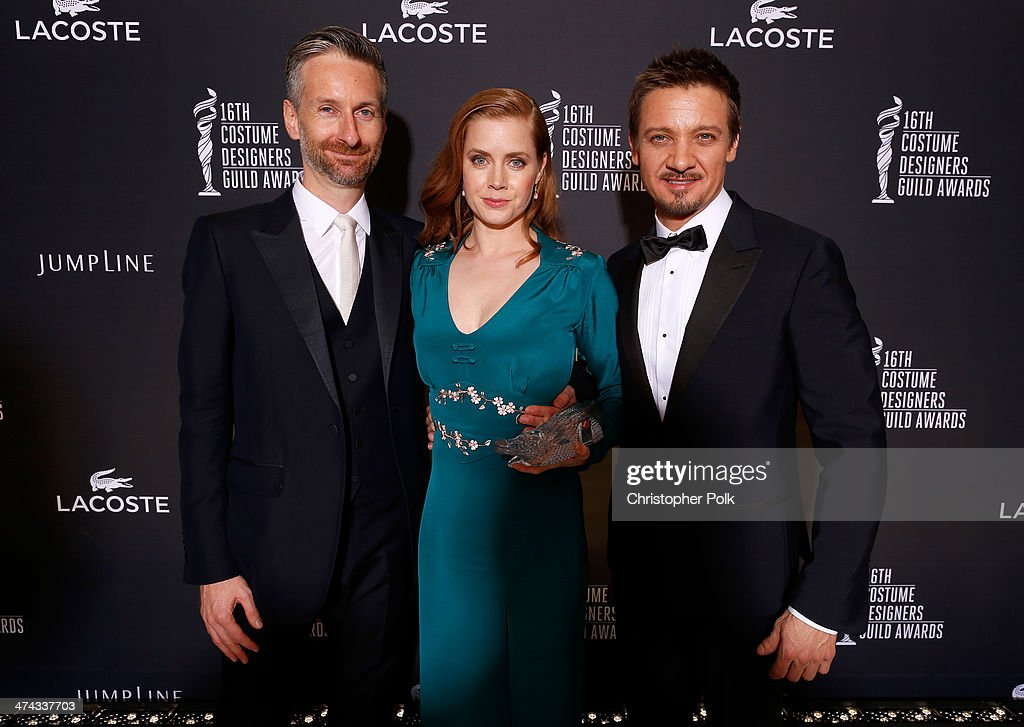 Costume designer Michael Wilkinson, honoree Amy Adams and actor Jeremy Renner pose with the Lacoste Spotlight Award during the 16th Costume Designers Guild Awards with presenting sponsor Lacoste at The Beverly Hilton Hotel on February 22, 2014 in Beverly Hills, California.