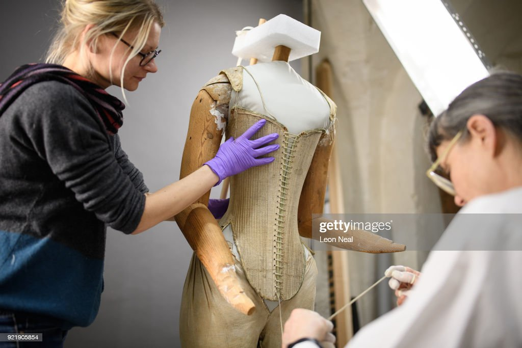 Costume historian Jenny Tiramani (R) fits a 'pair of straight bodies' to the funeral effigy of Elizabeth I at Westminster Abbey on February 20, 2018 in London, England. The bodice was supplied by the Queen's tailor, William Jones, to Elizabeth's own pattern and was made especially for the effigy which was carried on the hearse at her funeral in 1603. Among the details discovered during conservation work is that the boning finishes slightly lower on the right-hand side, allowing right-handed Elizabeth greater ease of movement. The corset will be among 300 objects from the Abbey collection on display in The Queen's Diamond Jubilee Galleries when they open at Westminster Abbey in June.