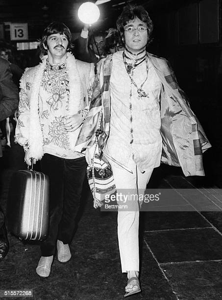 Costumed Beatles John Lennon and Ringo Starr carry luggage as they walk briskly through Euston Station here August 25th en route to train which will...
