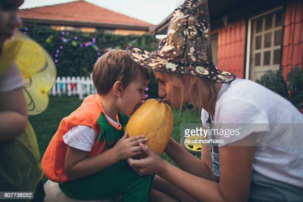 Costumed boy and his mom holding a pumpkin