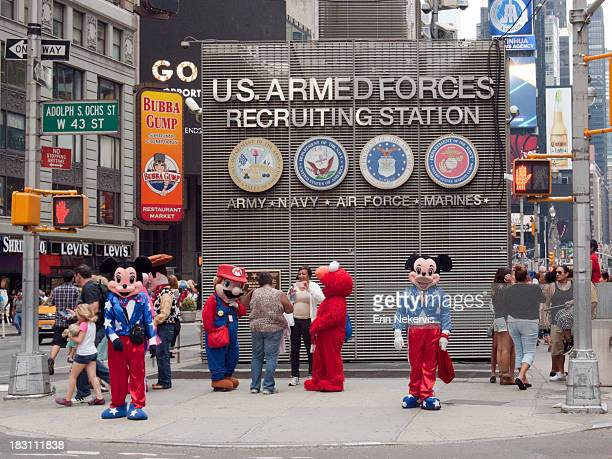 Costumed characters Mickey and Minnie Mouse, Super Mario and Elmo greet tourists in front of the Armed Forces Recruiting Station in Times Square...