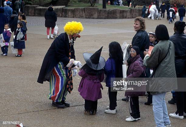 A costumed clown entertains children dressed in Halloween costumes at the Lincoln Park Zoo during a Halloween event Chicago Illinois 1980s