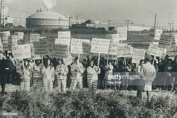 Costumed demonstrators wearing simulated prison uniforms stand in forefront of placardcarrying group waiting outside nuclear power station in...