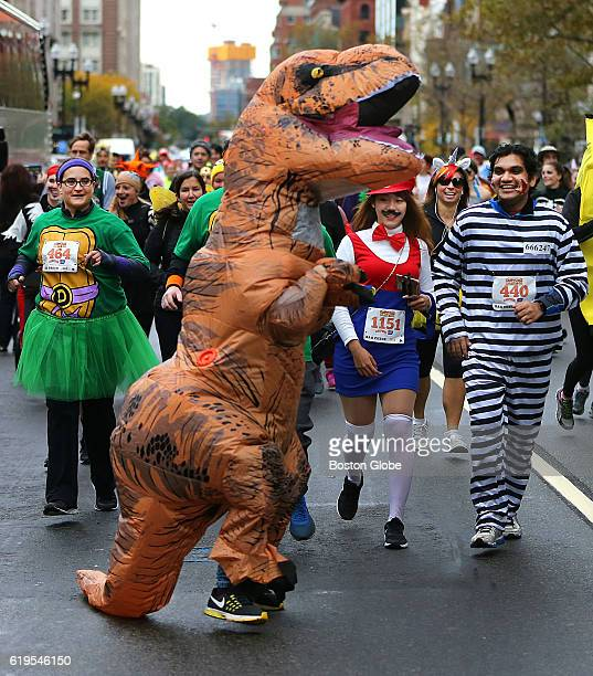 A costumed dinosaur along with other participants are dressed in Halloween costumes for the second annual Costume Dash 5k which started in Copley...