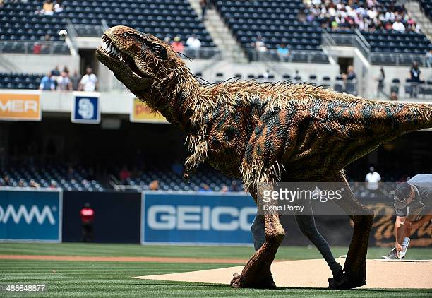 A costumed dinosaur Baby T from 'Walking with Dinosaurs' throws out the first pitch before a baseball game between the Kansas City Royals and the San...