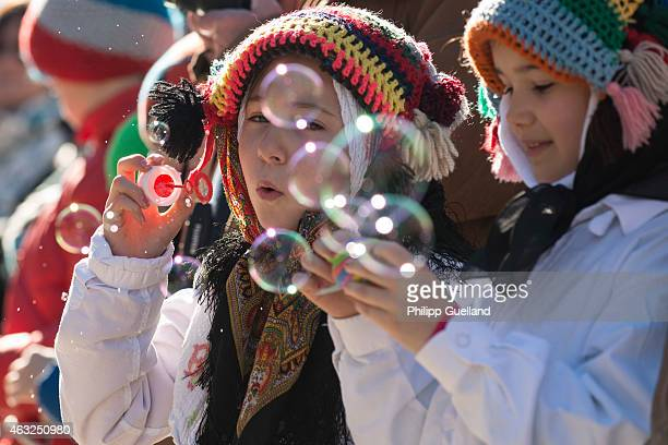 Costumed girls play with soap bubbles in the annual carnival parade on February 12 2015 in Mittenwald Germany The German Alpine Karwendel region...