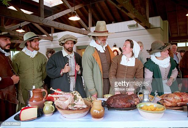 Costumed interpreters gather around a table loaded with food for the Harvest Feast of 1621 or The First Thanksgiving at Plimoth Plantation in...