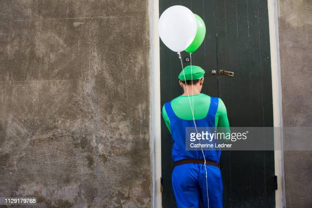Costumed man with balloons unlocking door to old carriage house
