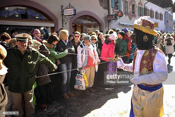 Costumed participant sprays spectators with water in the annual carnival parade on February 12 2015 in Mittenwald Germany The German Alpine Karwendel...